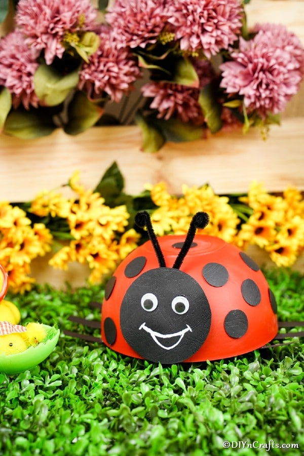 Ladybug craft in front of pink and yellow flowers