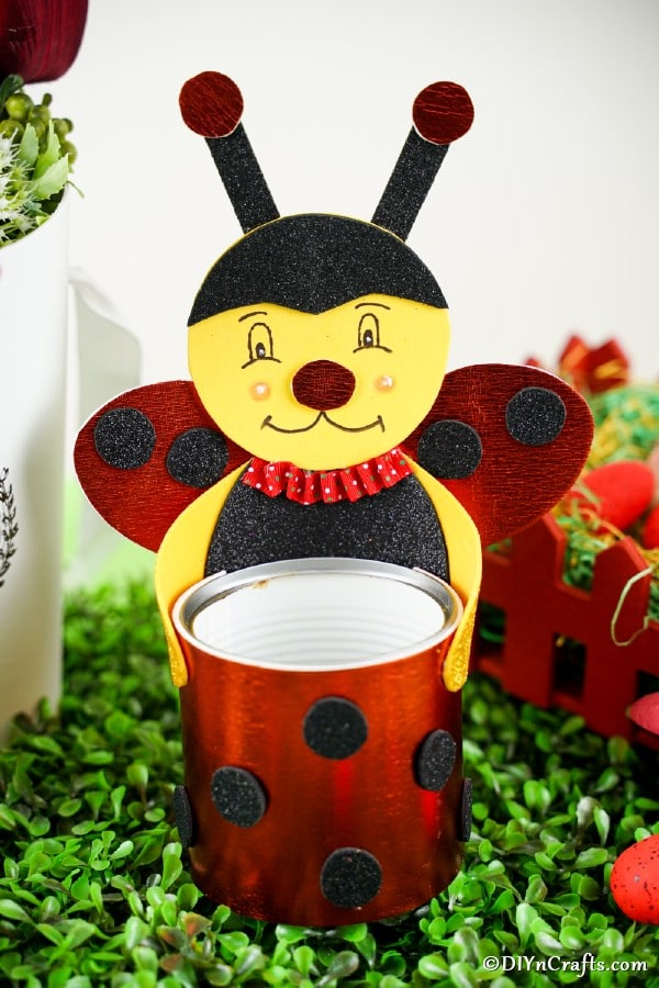 Upcycled tin can ladybug on fake grass