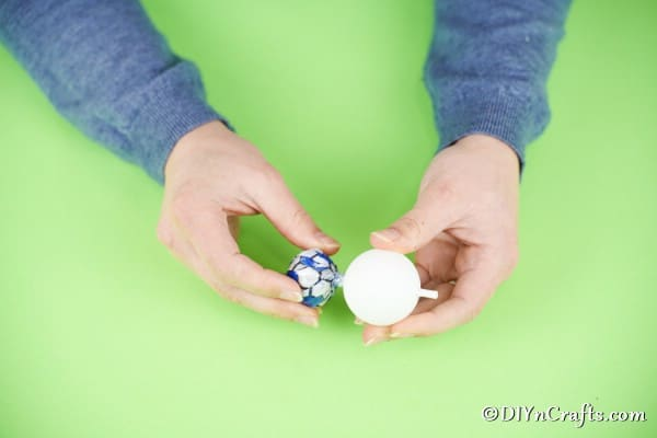 Pushing a lollipop into a ping pong ball