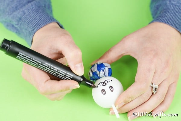 Drawing a face on the ping pong ball
