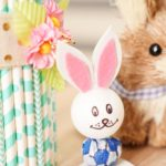 Lollipop bunny sitting by paper straw vase