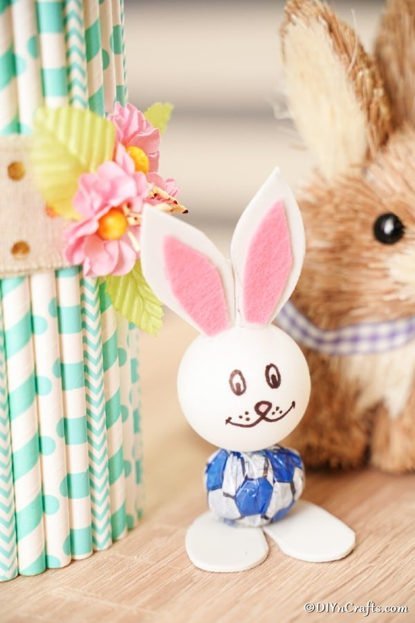 Lollipop bunny sitting by paper straw vase