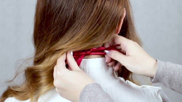 Tying hair tie behind hair