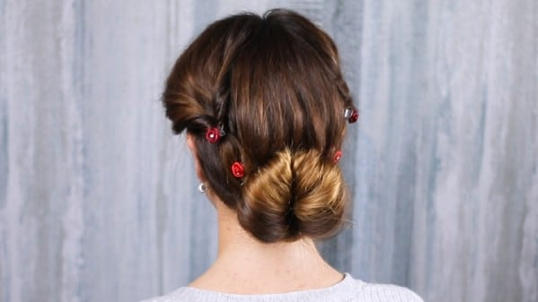 Brunette with low bun in front of grey background