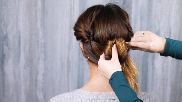 Pulling hair up to secure ponytail