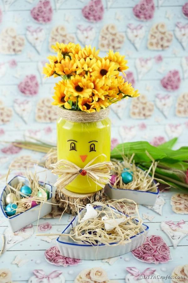 Mason jar vase in front of floral paper