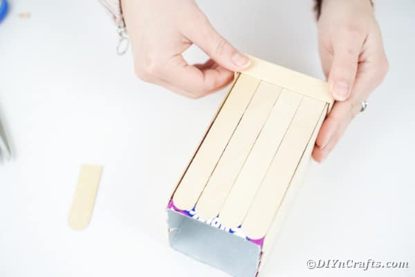 Gluing craft sticks around the bottom of the milk carton