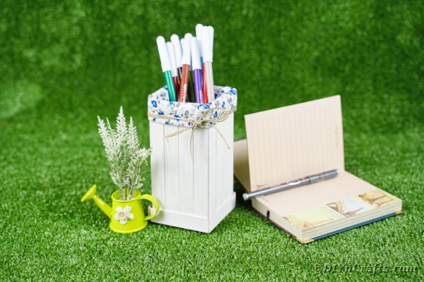markers in pencil holder on grass by book