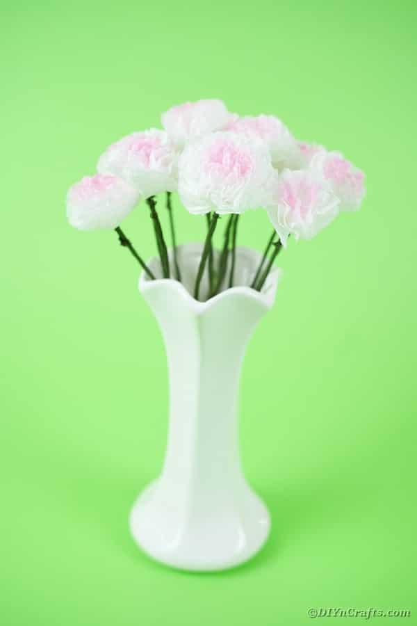 Tissue paper flowers in white vase on green background