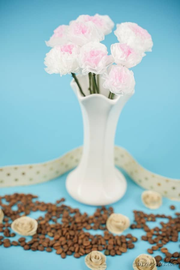 White vase of tissue paper flowers on blue counter