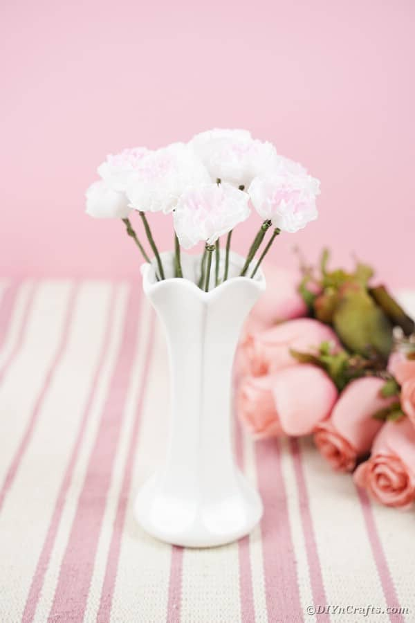 Paper flowers in white vase on pink table
