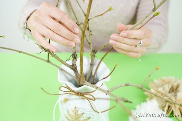 Arranging sticks in vase