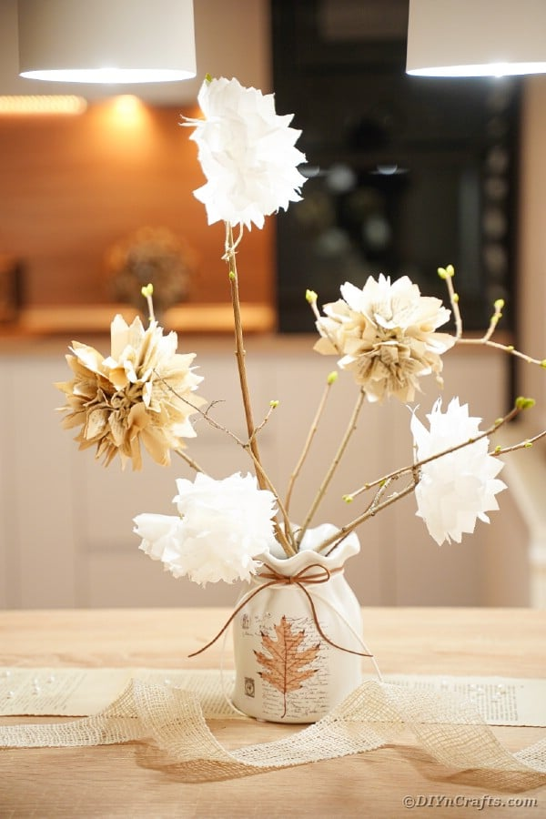 Vase filled with fake flowers on kitchen table
