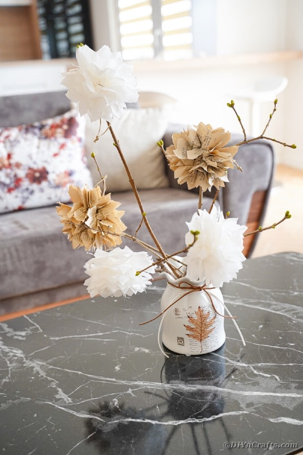 Small white container with rustic paper flower bouquet on marble table