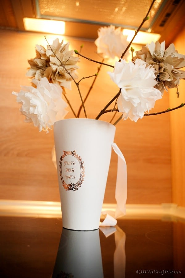 Cup filled with rustic paper flowers on table