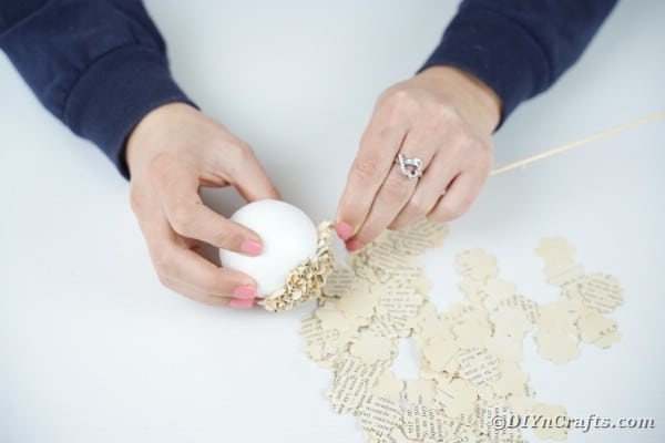 Gluing paper pieces to styrofoam ball