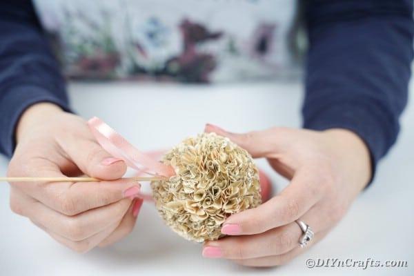 Gluing ribbon onto flower ball