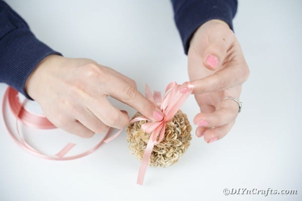 Gluing bow in place on flower ball