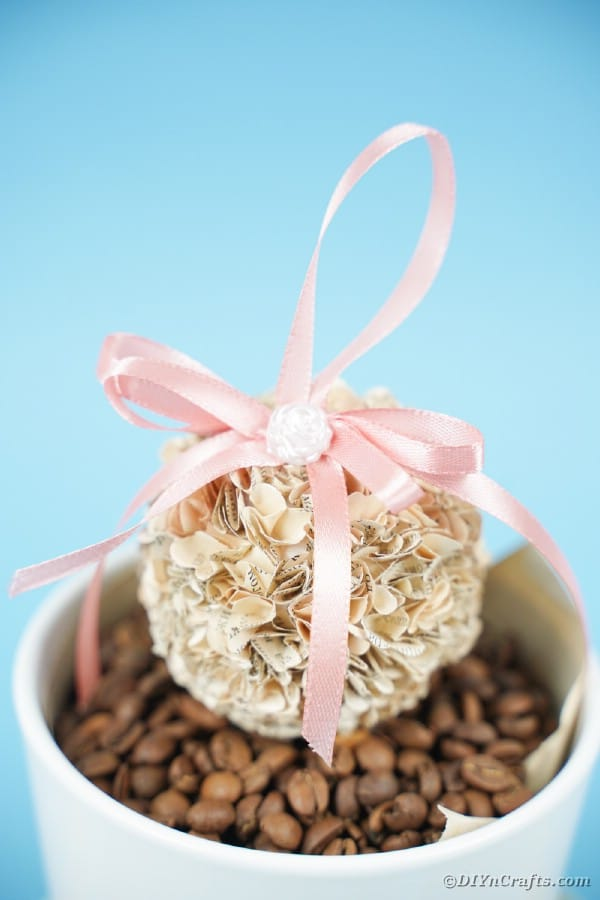 Paper flower ball on bucket with coffee beans