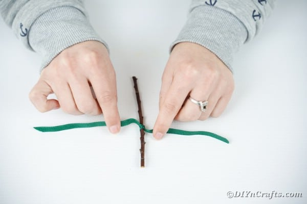 Tying green ribbon around twig