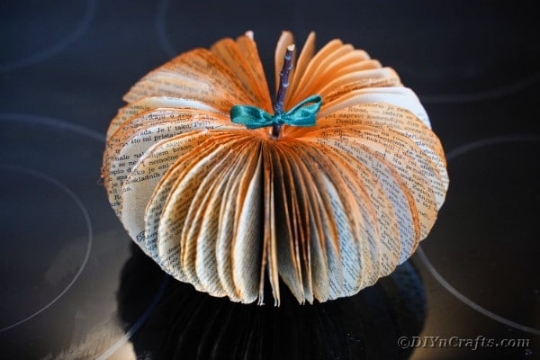 Paper pumpkin on black surface