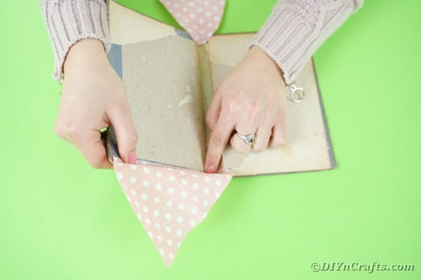 Gluing fabric onto sides of book