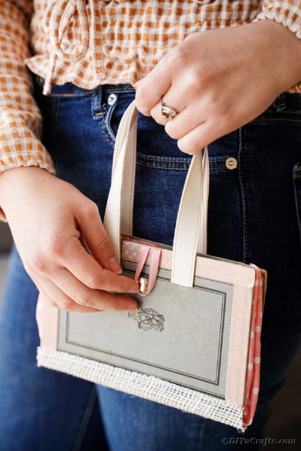 Woman in jeans holding old book purse