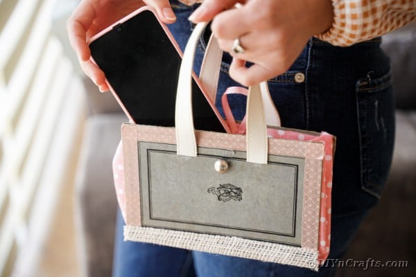 Woman adding phone to old book purse