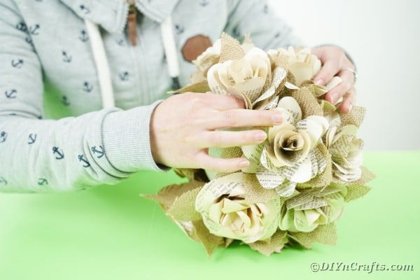 Adding flowers to burlap ball