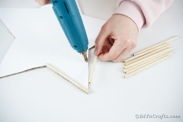 Gluing rolled paper onto wall art
