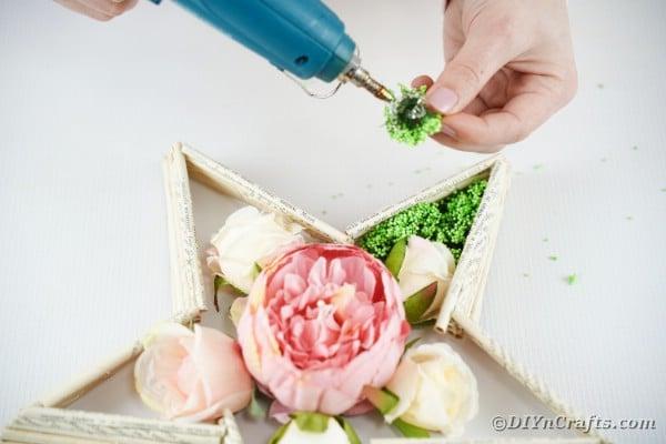 Gluing moss around flowers