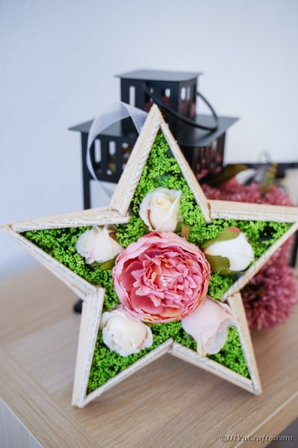 Old book page star on table by black lantern