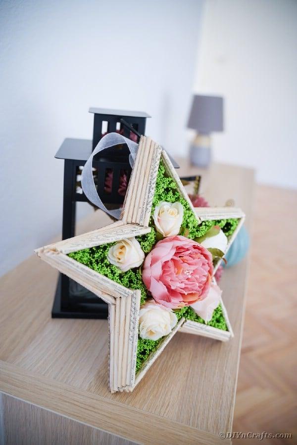 Paper star art against lantern on table
