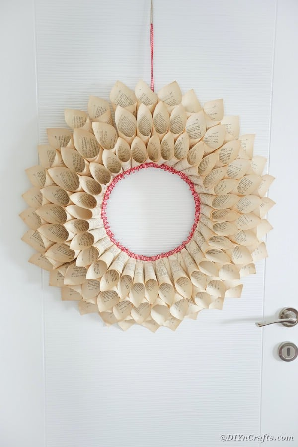 Upcycled book page wreath hanging on door