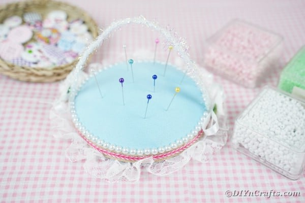 Old CD pincushion on pink gingham fabric