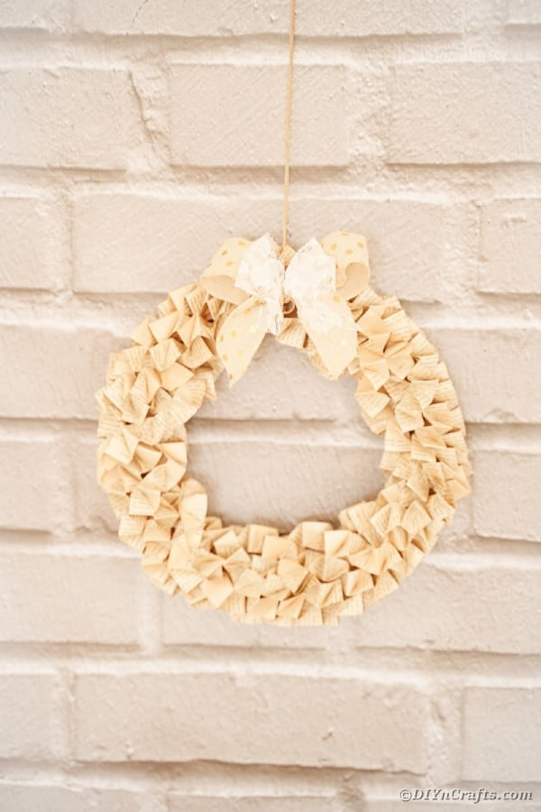 Origami book page wreath on brick wall