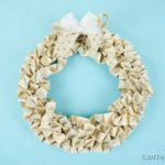 Origami book page wreath on blue wall