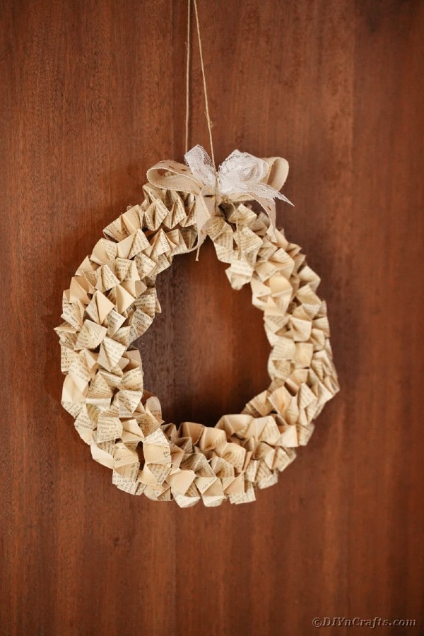 Book page wreath hanging on wooden wall
