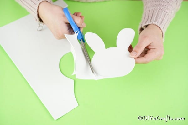 Cutting bunny head out of white paper