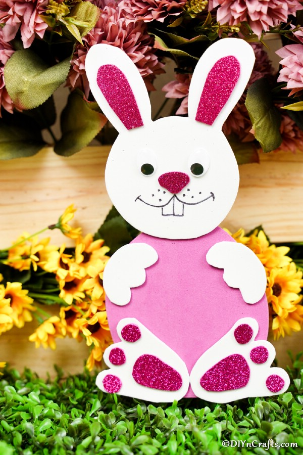 Foam pink bunny in front of yellow flowers