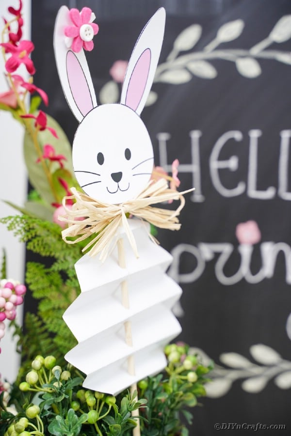 Paper bunny on a stick in front of chalkboard