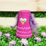 Plastic cup owl in front of wooden box