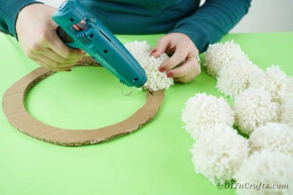 Gluing pom poms to cardboard circle
