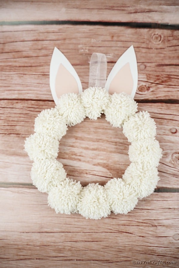 Pom Pom wreath against wooden background