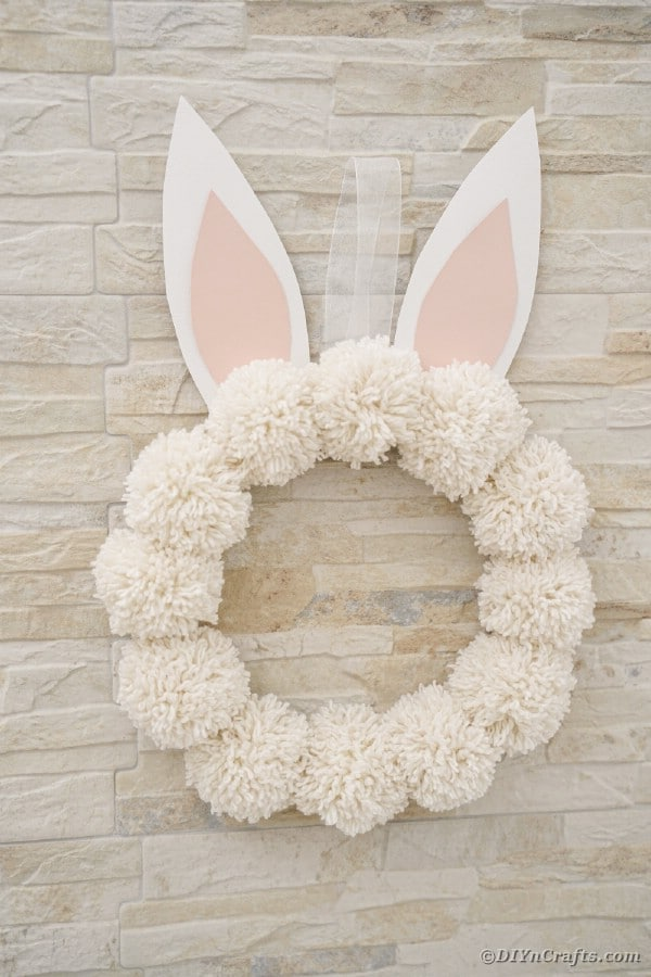 White bunny wreath hanging against brick