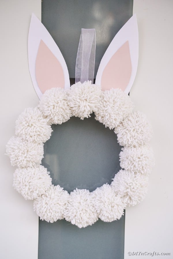 Yarn pom pom wreath hanging on door