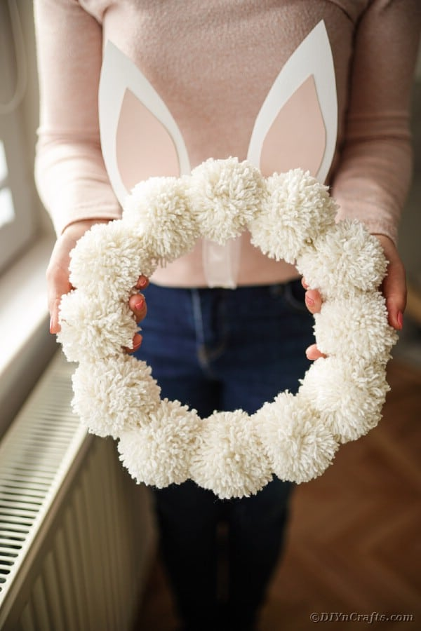 Woman holding easter pom pom wreath
