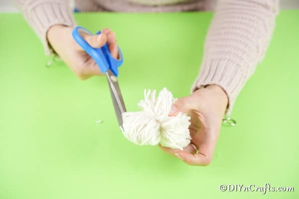 Cutting ends of pom pom to create fluff