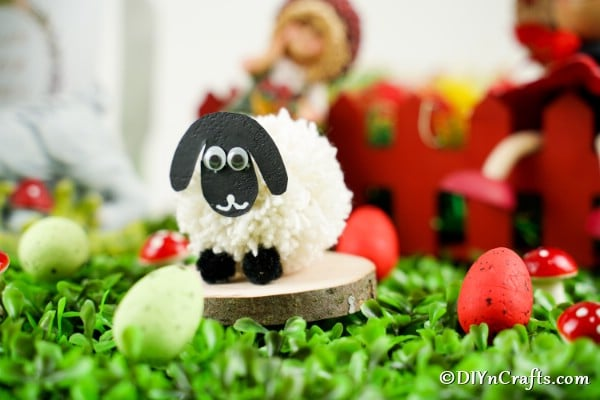 Sheep craft on fake grass and wood slice