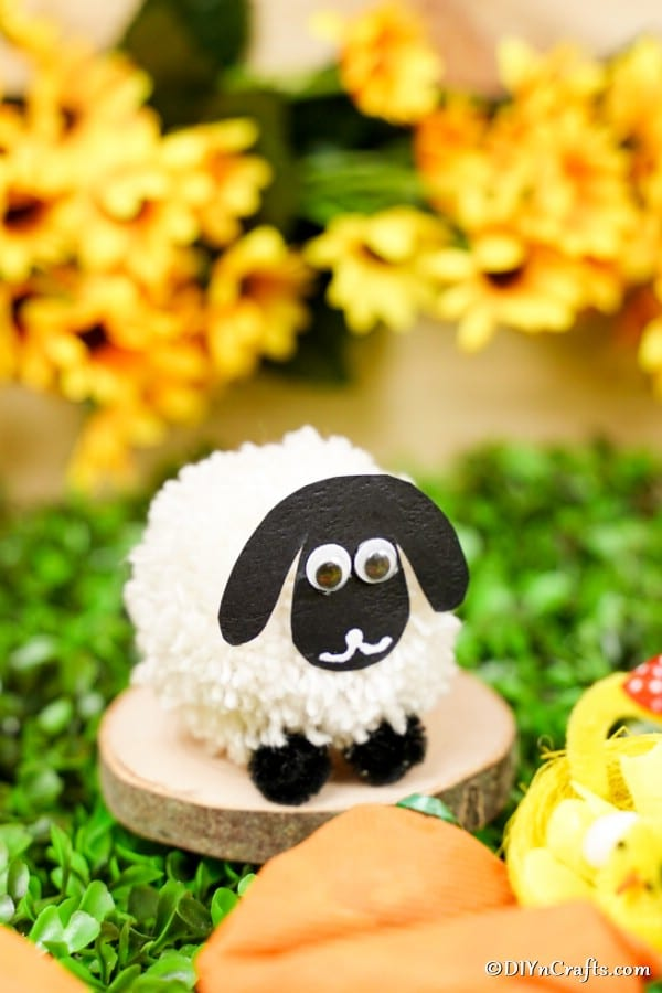 Pom Pom sheep on wooden slice with Easter decorations